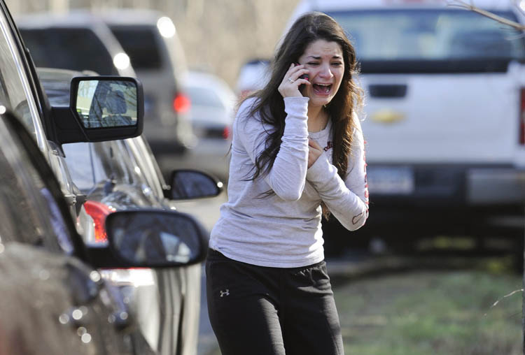 A woman waits to hear about her sister, a teacher, following a shooting at the Sandy Hook Elementary School in Newtown, Conn., about 60 miles (96 kilometers) northeast of New York City, Friday, Dec. 14, 2012. An official with knowledge of Friday's shooting said 27 people were dead, including 18 children. (Jessica Hill / The Associated Press)