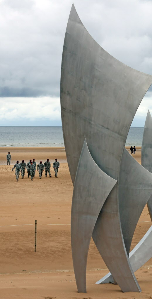 U.S. soldiers from the 82d airborne company from Fort Bragg, North Carolina, walk on the beach of Saint Laurent sur Mer, also called Omaha Beach, after collecting sand to take back to their country, Wednesday June 4, 2014.  World leaders and veterans prepare to mark the 70th anniversary of the D-Day invasion this week in Normandy. Visible at foreground right is The Brave monument.  (Remy de la Mauviniere / The Associated Press )