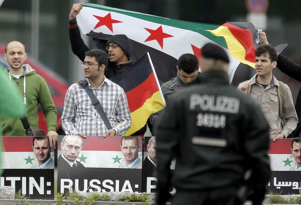 Demonstrators wave Syrian and German flags and show crossed-out portraits of Russian President Vladimir Putin and Syrian President Bashar Assad to demonstrate against the Syrian regime and the Russian Syria policy in front of the chancellery in Berlin. German Chancellor Angela Merkel is due to welcome President of Russia Vladimir Putin, both not pictured. The arrival of the Russian delegation is delayed. (AP Photo/Gero Breloer)