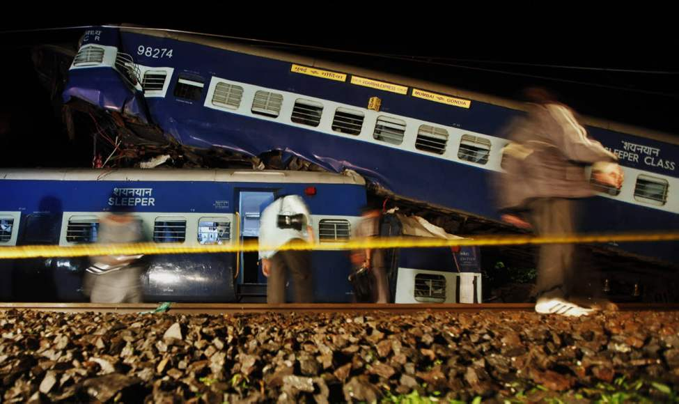 Indian people walk next to wrecked rail cars in Kasara, India. A fast moving express train collided with some derailed coaches of a commuter train that were lying on the tracks Thursday, according to Press Trust of India. (AP Photo/Rajanish Kakade)
