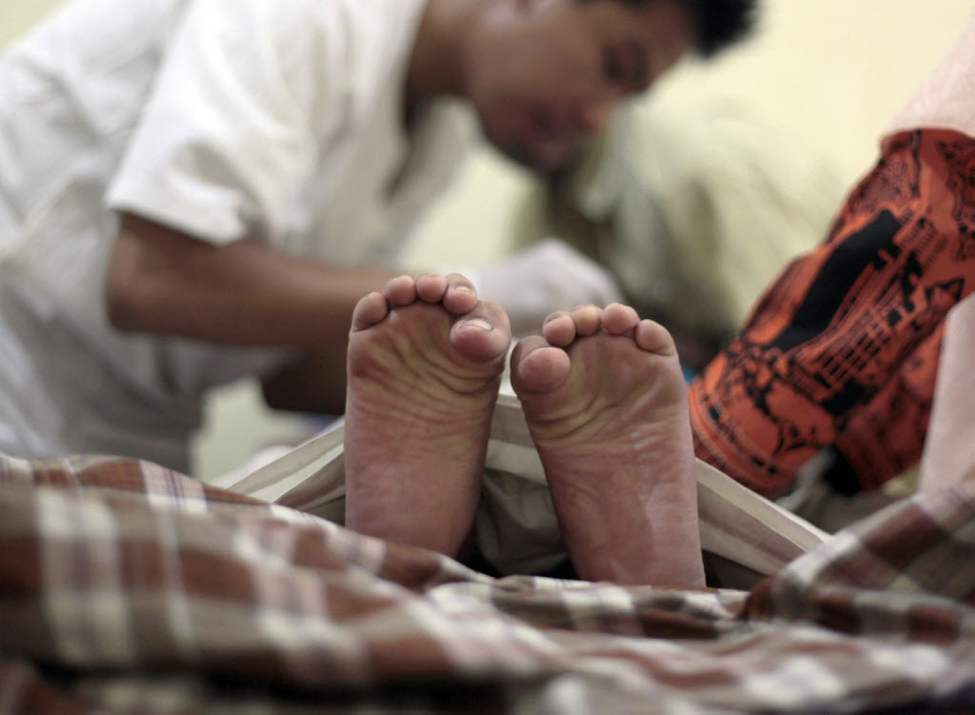 A boy's toes curl in pain as a doctor performs circumcision on him during a charge-free mass circumcision sponsored by a gubernatorial candidate in Jakarta, Indonesia. In accordance with Islamic tradition, Indonesian Muslim boys are circumcised before they reach puberty. Indonesia is the world's most populous Muslim country. (AP Photo/Dita Alangkara)