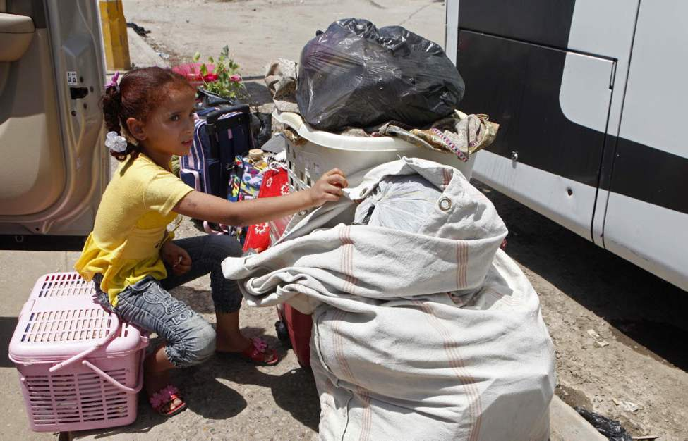 Layla Fadhil, an Iraqi refugee, sits with her family's belongings after her arrival from Syria to the Mansour neighborhood of Baghdad, Iraq. Iraq has flown hundreds of its citizens out of Damascus to escape the civil war in Syria, an official said Friday, while thousands of Iraqis poured through a major border crossing despite rebel takeovers of Syrian government posts and escalating violence near the two nations' boundaries. (AP Photo/Karim Kadim)