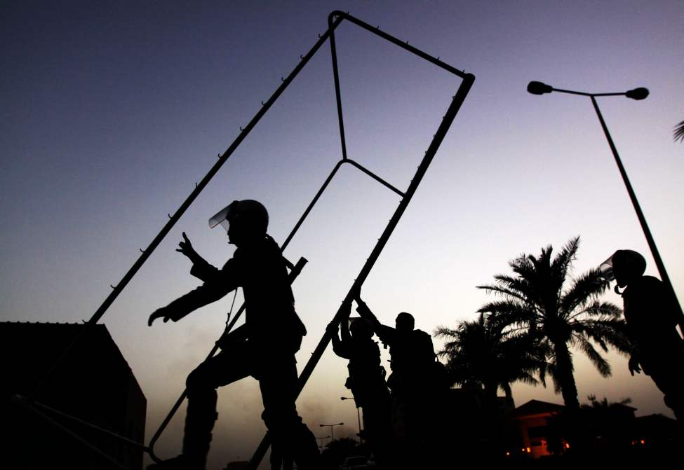 Riot police clear a soccer goal and other debris used as roadblocks by Bahraini anti-government protesters, unseen, to slow the police pursuing them during clashes Friday, June 8, 2012, in Abu Saiba, Bahrain. Riot police in Bahrain fired tear gas and stun grenades Friday as tens of thousands of protesters staged the biggest anti-government demonstrations in weeks in the divided Gulf nation. (Hasan Jamali / The Associated Press)