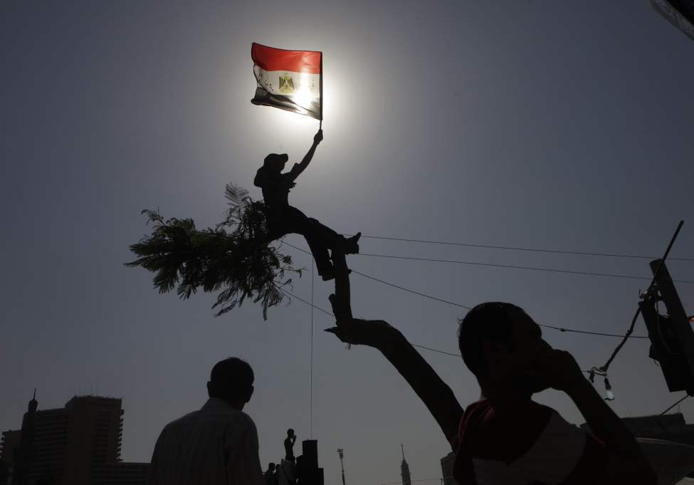 An Egyptian protester waves a national flag over a tree at Tahrir Square, Cairo, Egypt, Friday, June 8, 2012. Hundreds gathered in Cairo's Tahrir Square, the focal point of Egyptian uprising, to demonstrate against presidential candidate Ahmed Shafiq, Hosni Mubarak's last prime minister, ahead of a run-off vote.