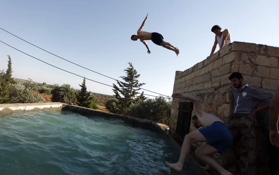 Free Syrian Army fighters swim in a pool on the outskirts of Aleppo, Syria, Tuesday, June 12, 2012. On Tuesday, Syrian forces pelted the eastern city of Deir el-Zour with mortars as anti-government protesters were dispersing before dawn Tuesday, killing several people, activists said. The offensives were part of an escalation of violence in recent weeks that has brought more international pressure on President Bashar Assad's regime faces over its brutal tactics against the opposition. The U.N. accused the government of using children as human shields in a new report.