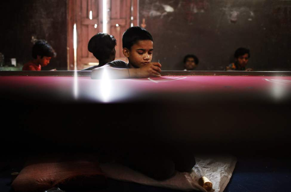 An Indian migrant boy works in a sari factory on World Day Against Child Labour in Katmandu, Nepal, Tuesday, June 12, 2012. This day serves as a catalyst for the growing worldwide movement against child labour.