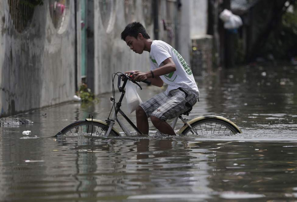 A Filipino pedals his bicycle along a flooded street in suburban Malabon, north of Manila. Heavy rains triggered floods in several areas in the metro forcing some schools to suspend classes in the morning as powerful typhoon Guchol exits the country towards southern Japan. (AP Photo/Aaron Favila)