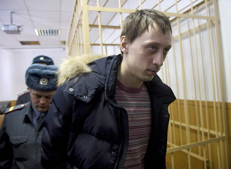 Pavel Dmitrichenko, foreground, is escorted out of a courtroom in Moscow, Russia, on Thursday, March 7, 2013. The star dancer is accused of masterminding the acid attack on the Bolshoi ballet chief.