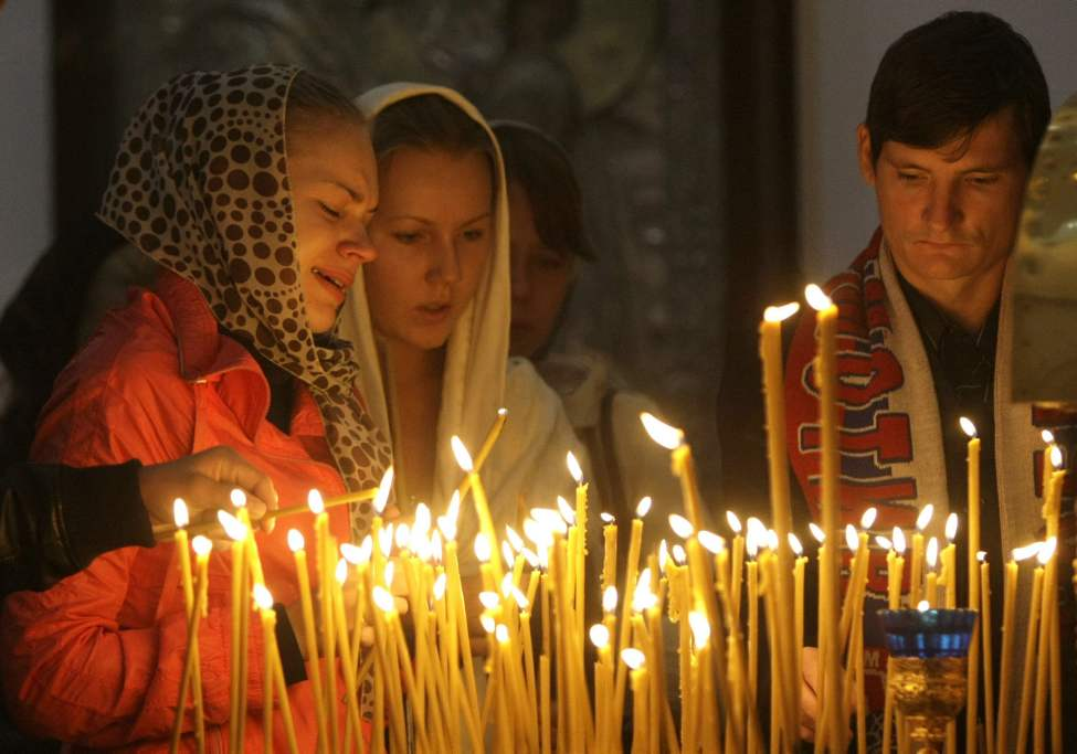Lokomotiv Yaroslavl fans and believers pray during a commemorative service at a church in Yaroslavl, Russia the day after the plane crash. (Misha Japaridze / The Associated Press archives)