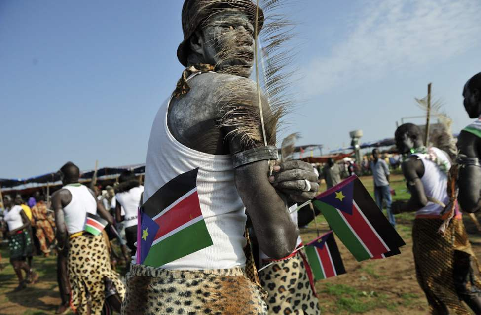 A man holds South Sudanese flags as he prepares to dance at the country's anniversary celebrations, at the John Garang mausoleum in Juba, South Sudan. The world's newest nation, South Sudan, is celebrating its first birthday. (AP Photo/Shannon Jensen)