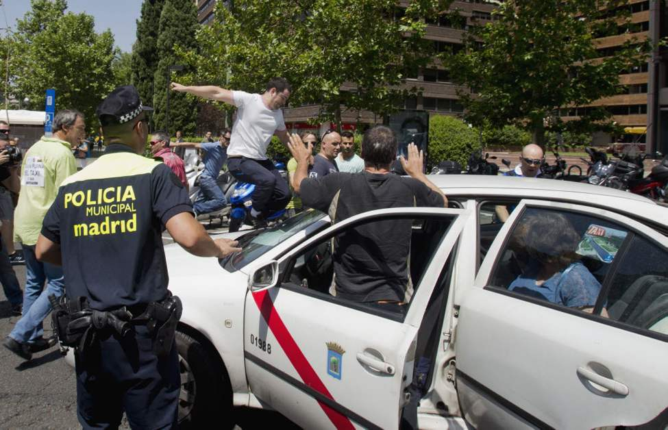 A taxi in service is attacked by other taxi drivers during a demonstration in Madrid, Spain. The taxi drivers are protesting the planned deregulation of the taxi sector. (AP Photo/Paul White)