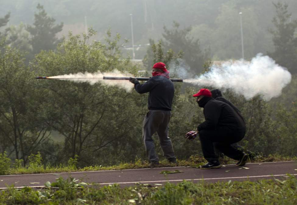 "Miners fire handmade rockets at riot police officers, unseen, as they defend their positions near the mine ""El Soton"" during clashes in El Entrego near Oviedo, Spain, Friday, June 15, 2012. Strikes, road blockades, and mine sit-ins continue as 8,000 mineworkers at over 40 coal mines in northern Spain continue their protests against government action to cut coal subsidies. (Emilio Morenatti / The Associated Press)"