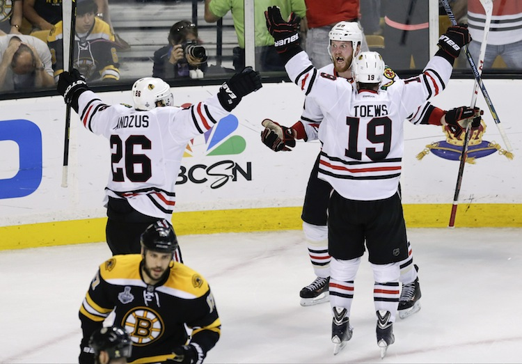 Chicago Blackhawks left wing Bryan Bickell (center) celebrates his goal with Chicago Blackhawks center Jonathan Toews Michal Handzus during the third period in Game 6 of the NHL Stanley Cup Finals against the Boston Bruins Monday. Bickell's game tied the game 2-2 late in the third period before teammate Dave Bolland potted the winner with less than a minute to play. (Charles Krupa / The Associated Press)
