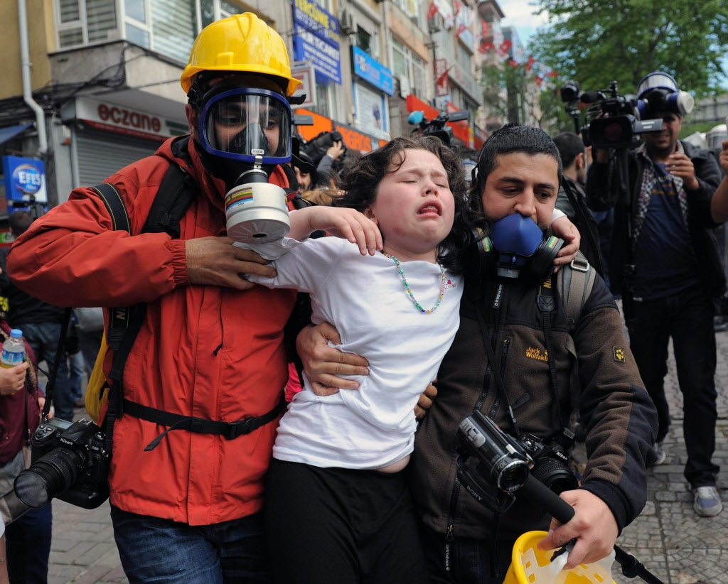 People help a child affected by tear gas as riot police use water cannons and tear gas to disperse thousands of people trying to reach the city's main Taksim Square to celebrate May Day in Istanbul, Turkey on Thursday. Clashes erupted between May Day demonstrators and riot police as crowds determined to defy a government ban tried to march to the city's iconic Taksim Square and were pushed back with water cannons and tear gas.  (Emrah Gurel / The Associated Press)