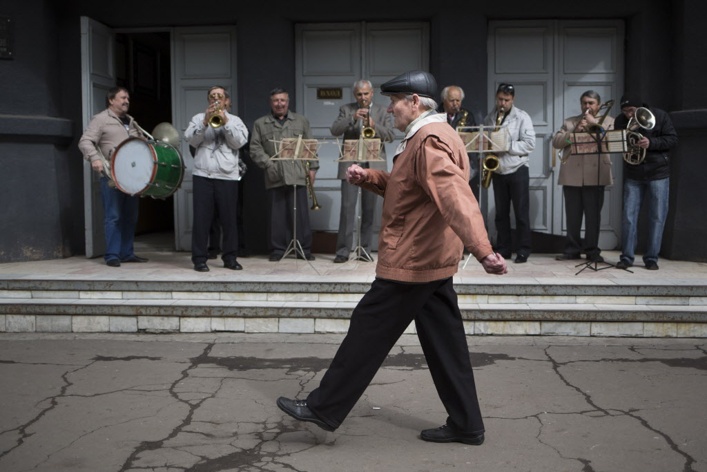 An elderly man marches in front of an amateur band while local citizens gather to mark May Day in Slovyansk, eastern Ukraine on Thursday. Russian state news media were quick to dismiss the protests as the work of Ukrainian neo-Nazis, a particularly loaded accusation because Ukrainian nationalists collaborating with the Nazis are blamed for horrific reprisal attacks during the Second World War. (Alexander Zemlianichenko / The Associated Press)
