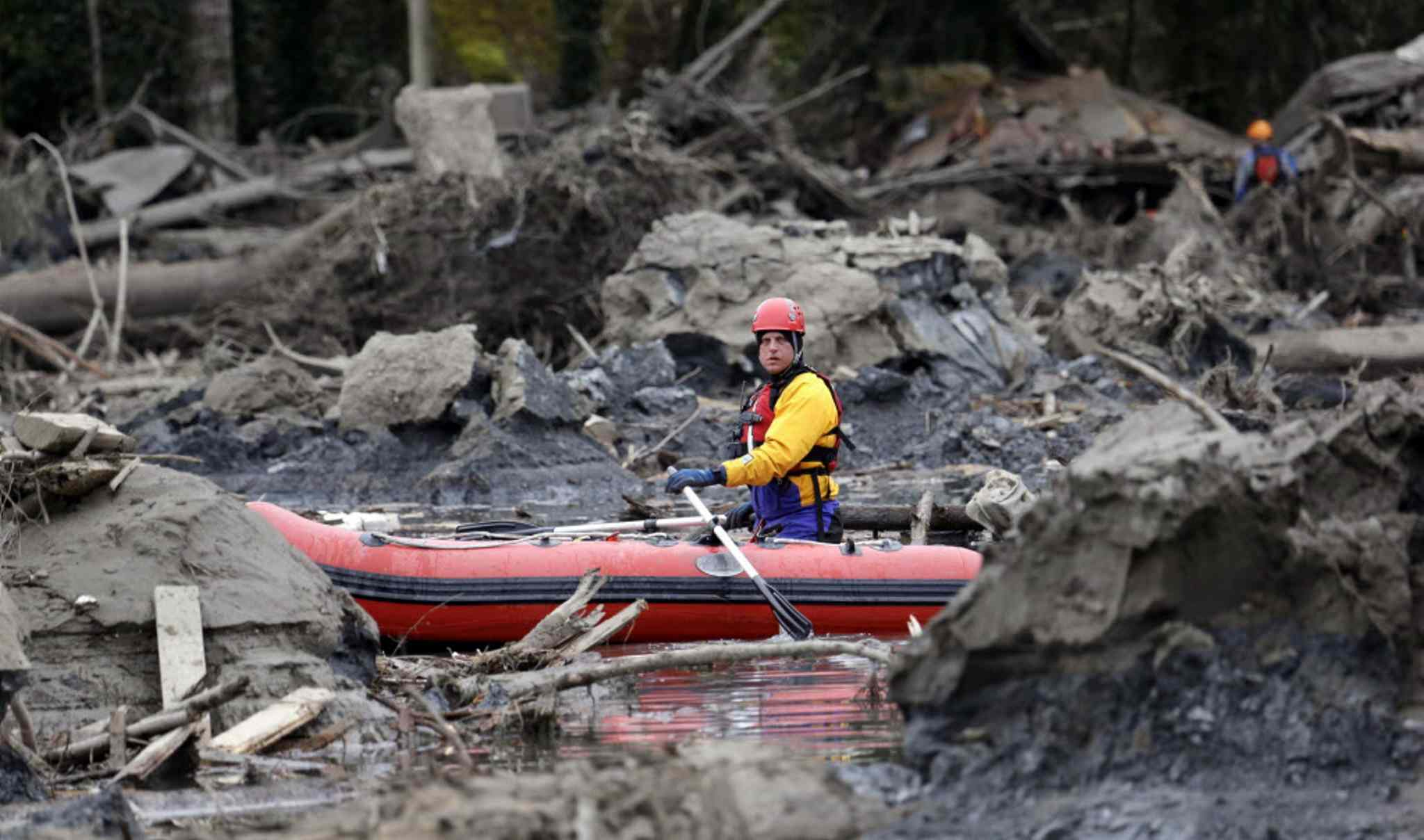 A searcher uses a small boat to look through debris from the deadly mudslide. At least 14 people were killed in the 1-square-mile slide that hit in a rural area about 55 miles northeast of Seattle on Saturday. Several people also were critically injured, and homes were destroyed.
