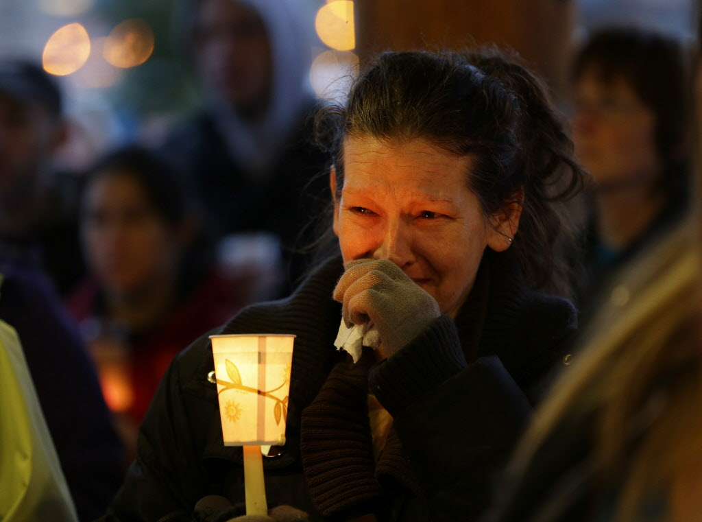 Teresa Welter cries as she holds a candle at a candlelight vigil in Arlington, Wash., for the victims of the massive mudslide that struck the nearby community of Oso, Wash., killing at least 16 people and leaving dozens missing.  (Ted S. Warren / The Associated Press)