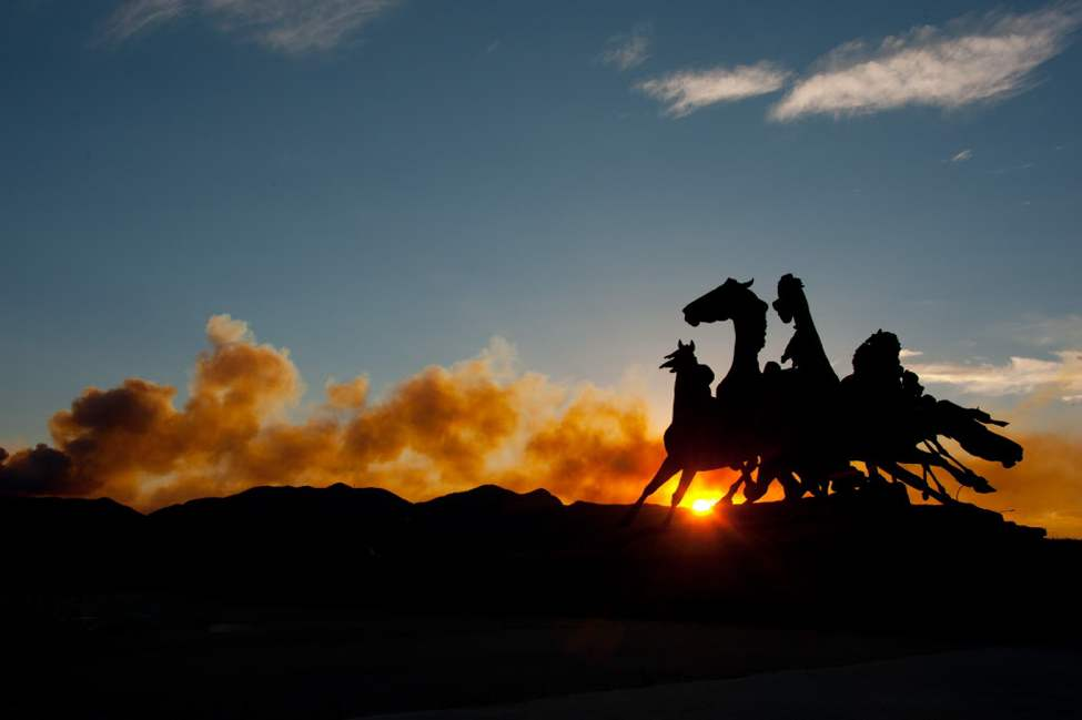 "T.D. Kelsey's ""Briargate Mustangs"" sculpture is silhouetted as smoke rises at sunset from the Waldo Canyon Fire burning west of Colorado Springs. The fire, one of at least a half-dozen wildfires in Colorado as of Monday, has blackened 5.3 square miles and displaced about 6,000 people since it started Saturday. (AP Photo/The Colorado Springs Gazette, Mark Reis)"