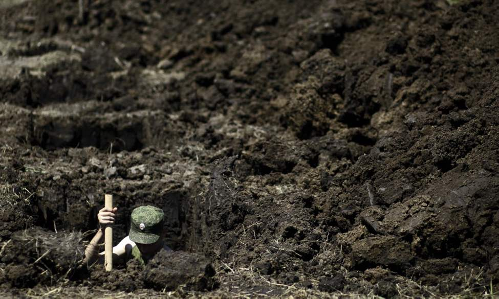 A soldier digs a grave for those who died during floods in Krymsk, south of Moscow. Intense flooding in the Black Sea region killed nearly 170 people Saturday. (AP Photo/Sergey Ponomarev)