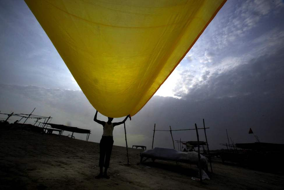 A Hindu holy man dries a piece of cloth on the banks of the River Ganges as monsoon clouds hover over in Allahabad, India. Monsoon rains that hits India usually from June to September are crucial for farmers whose crops feed hundreds of millions of people. (AP Photo/Rajesh Kumar Singh)