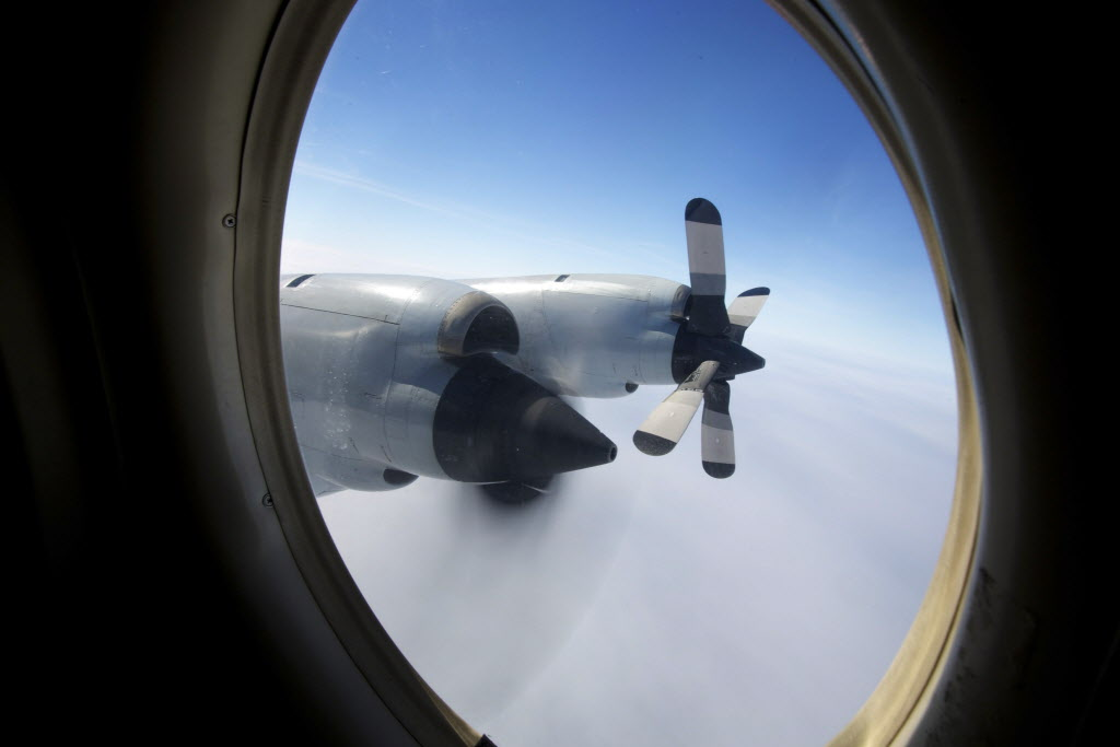 In this Monday, March 24, 2014 photo, one engine of an RAAF AP-3C Orion is shut down to conserve fuel whilst in a holding pattern at altitude above the search site on what was to be an 11-hour search mission for missing Malaysia Airlines Flight MH370 over the Indian Ocean. (Richard Wainwright / Pool / The Associated Press)