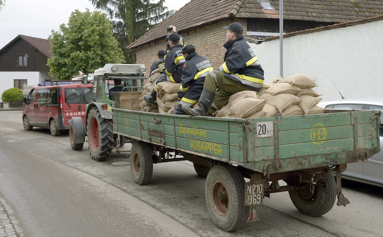 Firefighters sit on a tractor loaded with sandbags in Theiss, located west of Vienna in Austria. (Hans Punz / The Associated Press)