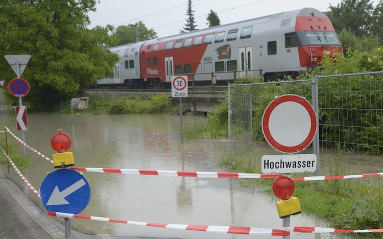 A street that leads to a tunnel under the railway in Kritzendorf near Vienna, Austria, is flooded out. The road sign reads 'Flood.'