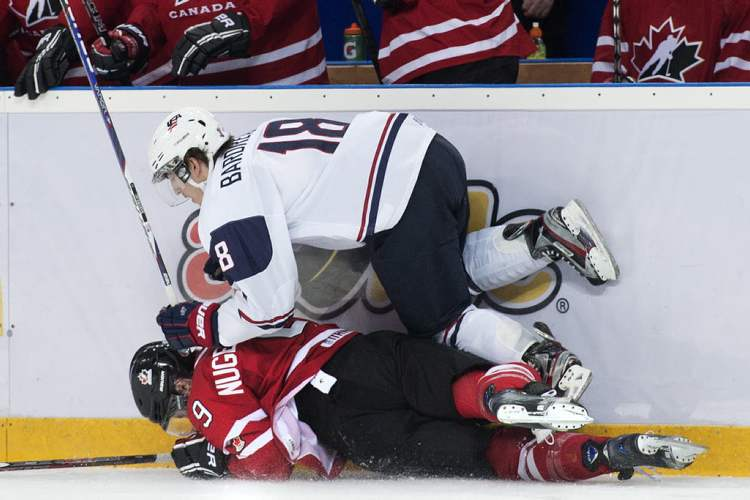 Team Canada forward Ryan Hugent-Hopkins gets run down by Team USA forward Cole Bardreau in second-period action Sunday.