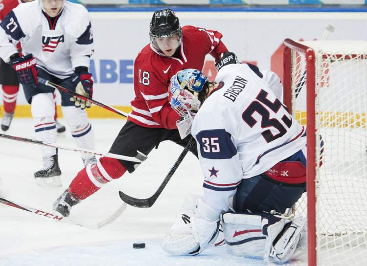 Team Canada forward Ryan Strome (left) gets stopped by Team USA goalie John Gibson during second period play Sunday.