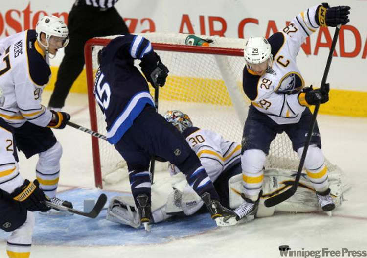 Buffalo captain Jason Pominville recovers a rebound after the Winnipeg Jets' Tanner Glass (15) tried to put one behind Sabres goalie Ryan Miller in first-period action Thursday at the MTS Centre.