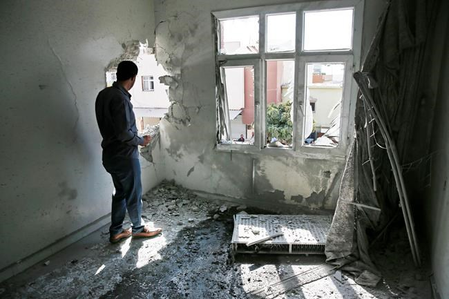 A person inspects the damage on a building hit by a mortar fired from inside Syria, in Akcakale, Sanliurfa province, southeastern Turkey, Sunday, Oct. 13, 2019. Incoming shells fired from northeastern Syria hit the house earlier on Sunday. Two residents were at the house and were evacuated. (AP Photo/Lefteris Pitarakis)