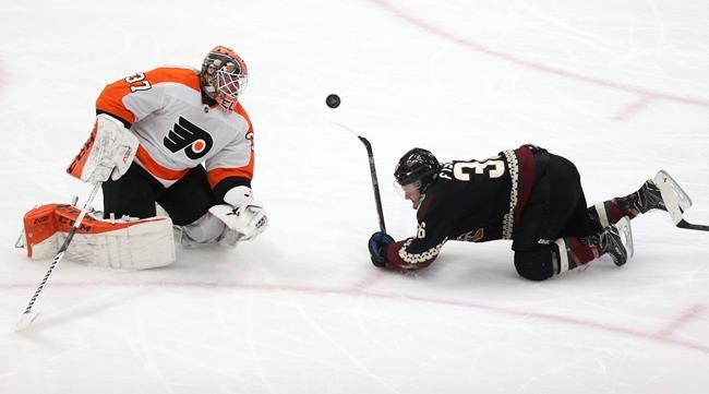 Philadelphia Flyers goalie Brian Elliott (37) watches the puck as it comes off Arizona Coyotes' Christian Fischer's (36) stick during the second period of an NHL hockey game Saturday, Jan. 4, 2020, in Glendale, Ariz. (AP Photo/Darryl Webb)