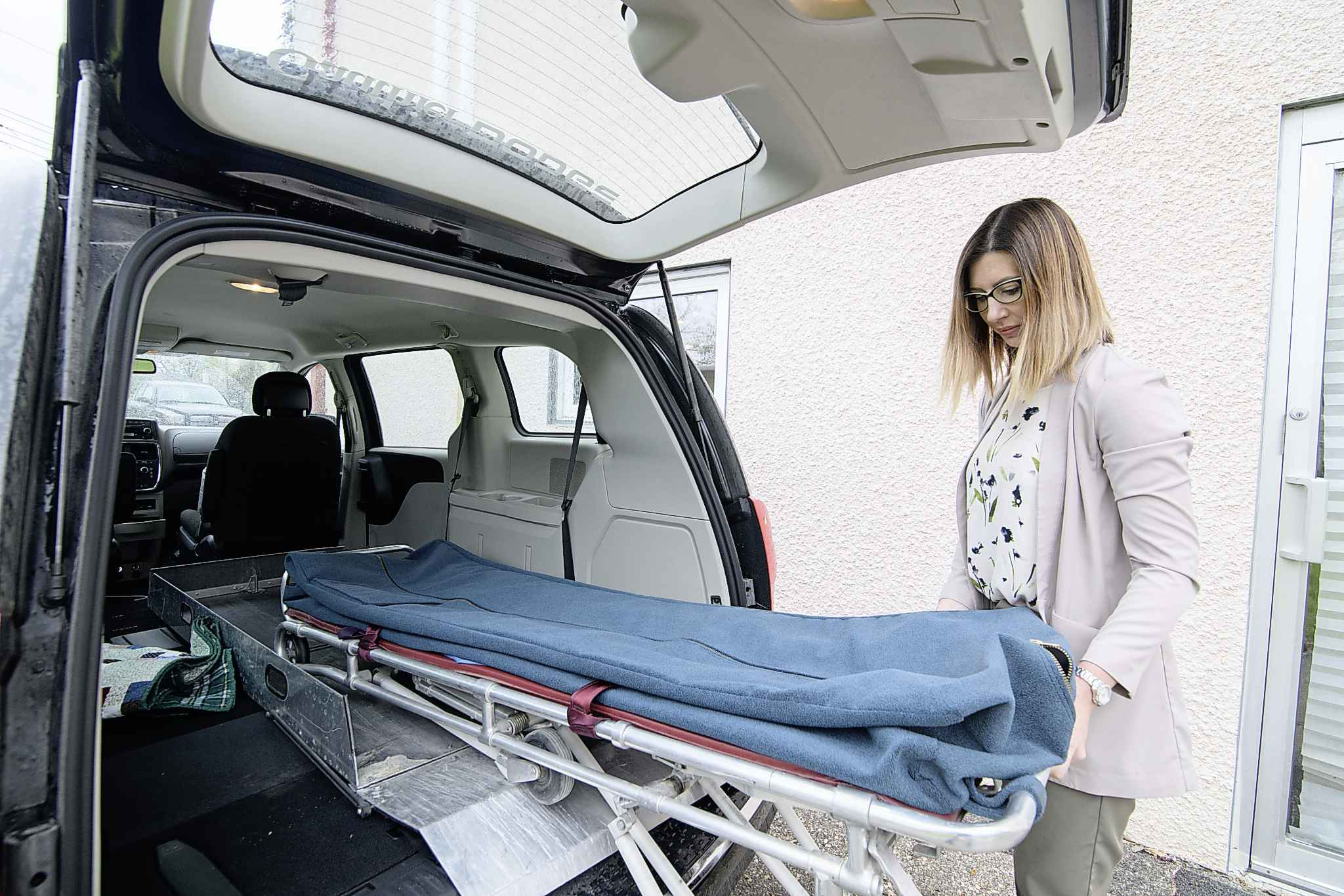 """Mike Sudoma / Winnipeg Free Press</p><p>Newton pulls the stretcher out of her modified minivan. """"If someone dies, I have to go pick them up myself,"""" she says.</p>"""
