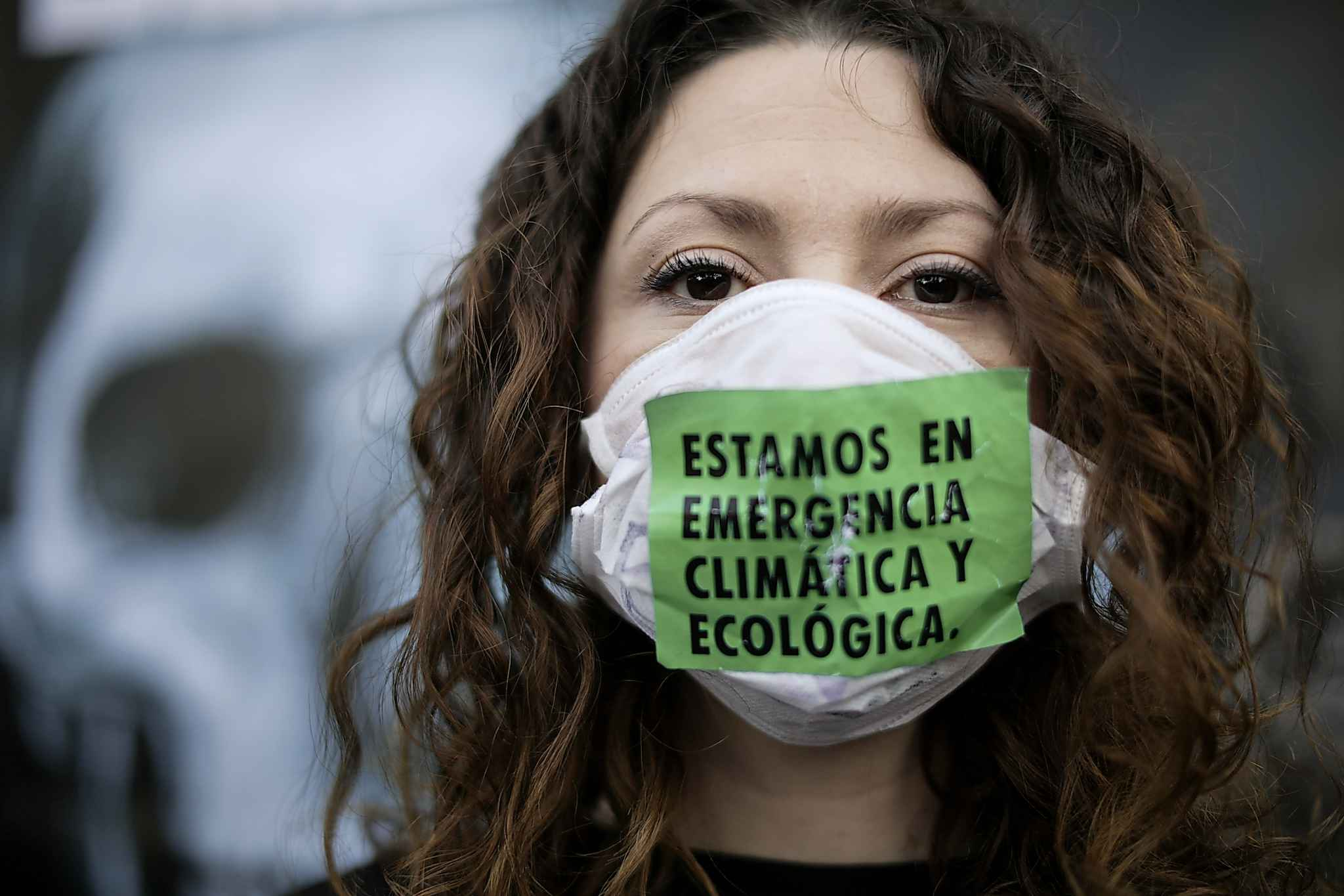 "A woman with a sign over her mask that reads in Spanish ""We are in a climate and ecologic emergency."""