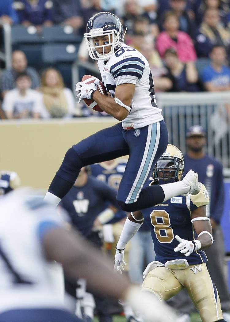Toronto Argonauts' Spencer Watt grabs a pass from Ricky Ray during the first half of the game.
