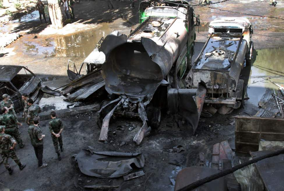 Syrian soldiers investigate the scene after a bomb attached to a fuel truck exploded outside a Damascus hotel where U.N. observers are staying. Several  people were wounded, Syria's state TV reported. TV said the explosion took place near a parking lot used by the army command, which is about 300 metres away. (AP Photo/Bassem Tellawi)
