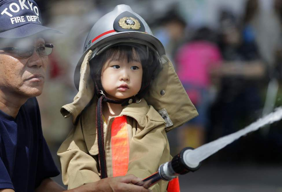 A girl is helped by a firefighter to hose during a firefighting drill in Tokyo . (AP Photo/Shizuo Kambayashi)
