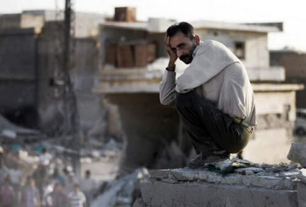 In this citizen journalism image provided by Shaam News Network SNN, taken on Wednesday, a Syrian man reacts after an air strike destroyed at least ten houses in the town of Azaz on the outskirts of Aleppo, Syria. (AP Photo/Shaam News Network, SNN)