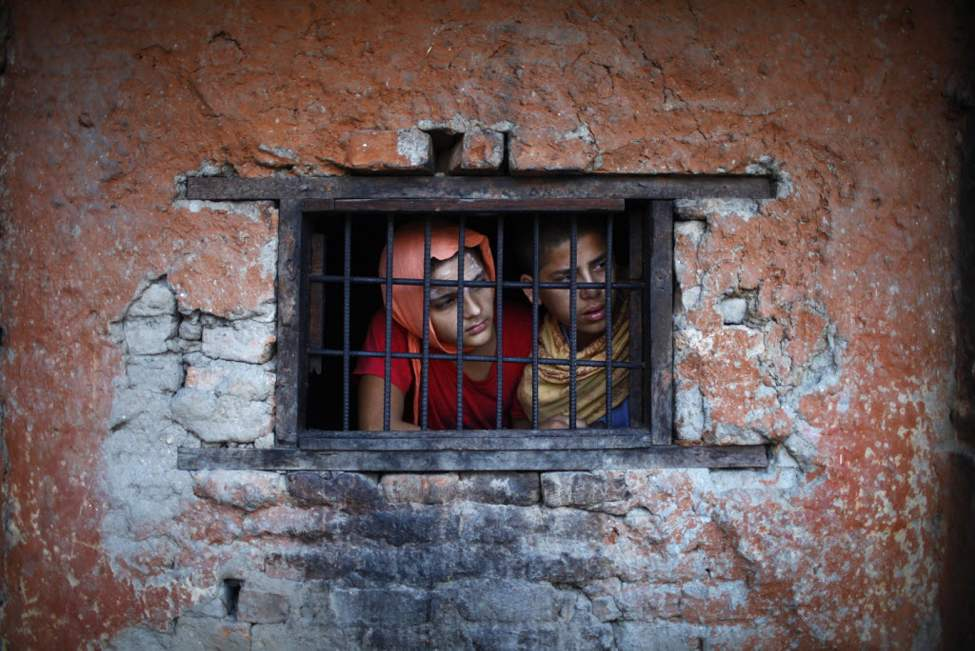 Students from Pashupatinath Veda Vidya Ashram, a school on Hindu religious teaching, look out from a window of their class in Katmandu, Nepal. (AP Photo/Niranjan Shrestha)