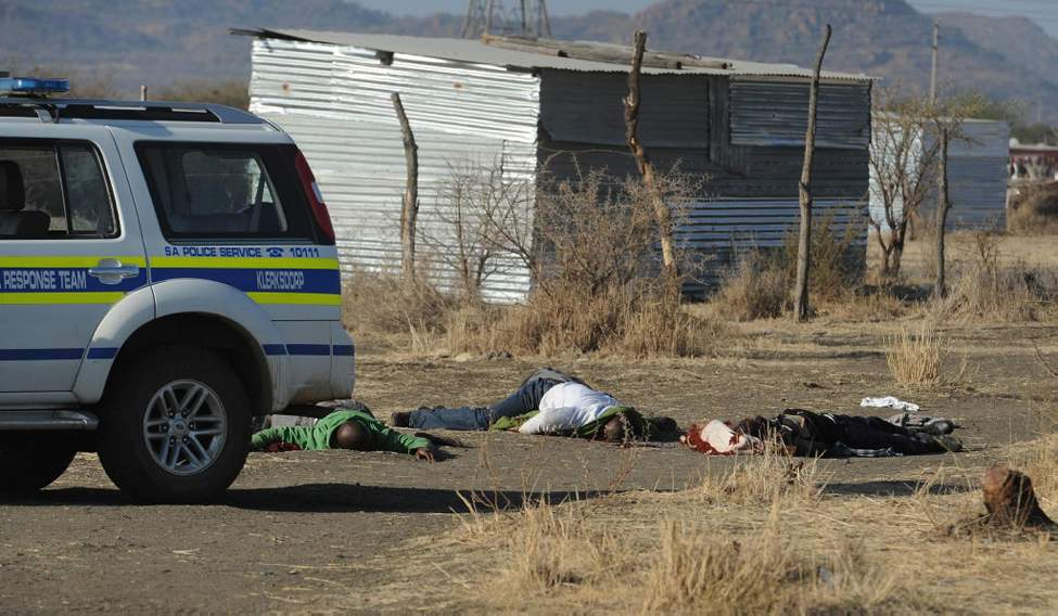 Bodies of striking miners lay on the ground after police opened fire on a crowd at the Lonmin Platinum Mine near Rustenburg. South African police opened fire Thursday on a crowd of striking workers at a platinum mine, leaving an unknown number of people injured and possibly dead. (AP Photo)