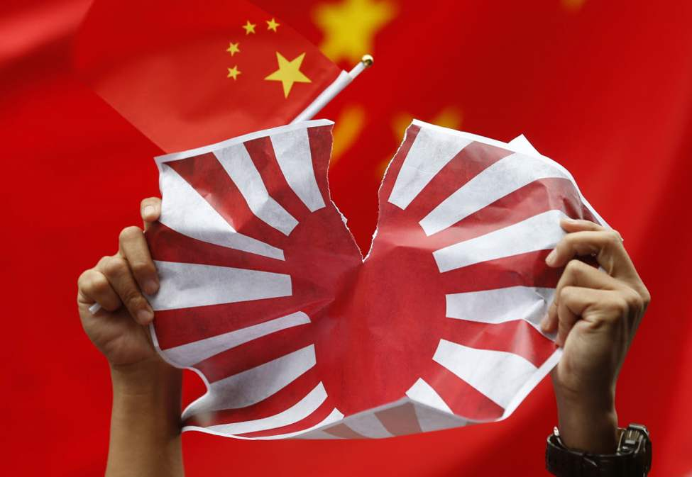 An anti-Japan protester tears Japanese Rising Sun Flag during a rally outside the Japanese Consulate General in Hong Kong as they demand Japanese government to release Chinese activists arrested in Japan after landing on Uotsuri Island, one of the islands of Senkaku in Japanese and Diaoyu in Chinese. Japan is considering deporting 14 Chinese activists arrested for landing without authorization on disputed islands in the East China Sea, as harsh criticisms and repeated demands for their release erupted Thursday in China. (AP Photo/Kin Cheung)