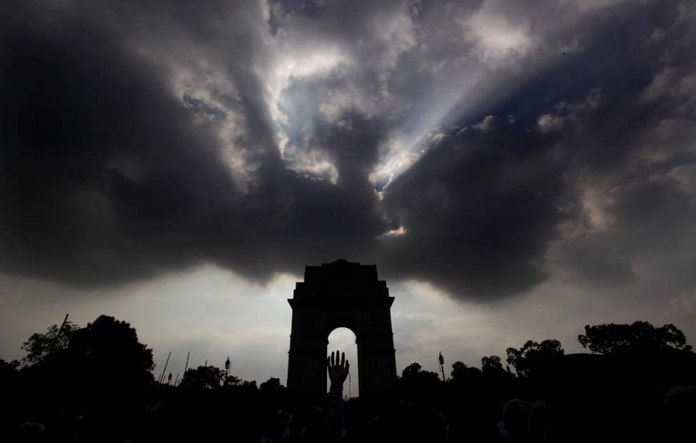 Monsoon clouds hover over India Gate monument as a person waves, in New Delhi, India. (AP Photo/Manish Swarup)