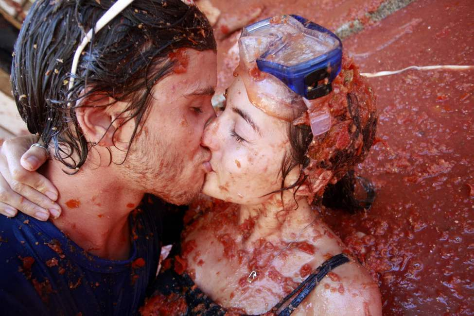 """Revelers kiss each other during the annual """"Tomatina"""" tomato fight fiesta in the village of Bunol, near Valencia, Spain. Bunol's town hall estimated more than 40,000 people, some from as far away as Japan and Australia, took up arms Wednesday with 100 tons of tomatoes in the yearly food fight known as the 'Tomatina' now in its 64th year. (AP Photo/Alberto Saiz)"""