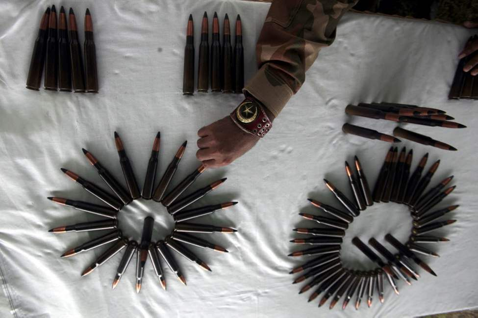 A Pakistani army soldier arranges ammunition reportedly recovered from hideouts of militants in tribal areas, as they are displayed in Peshawar, Pakistan. (AP Photo/Mohammad Sajjad)