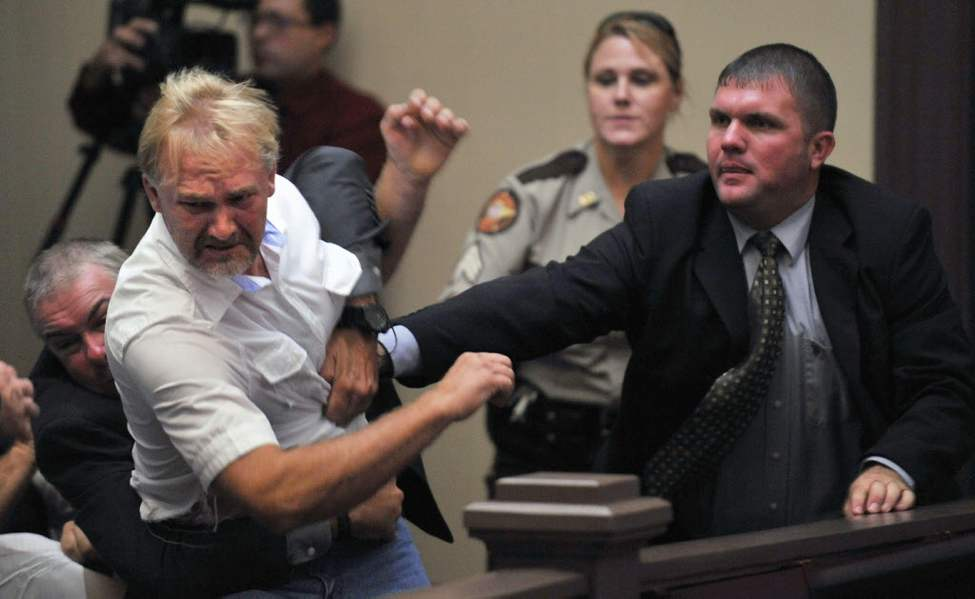 Wesley Thomas, the step father of Tiffany York, is tackled by courtroom security during the hearing of defendant Sgt. Anthony Peden at Long County Superior Court, in Ludowici, Ga. District Attorney Tom Durden announced in court that he will seek the death penalty for Peden, Pvt. Isaac Aguigui, and Pvt. Christopher Salmon. The three Fort Stewart soldiers are accused of malice murder, felony murder and criminal gang activity in the Dec. 4 slayings of former soldier Michael Roark and his girlfriend, 17-year-old Tiffany York. The two were found shot to death off a dirt road near the Army post. Prosecutors say the accused men were part of a militia operating within the U.S. Army that was stockpiling weapons and wanted to overthrow the federal government. (AP Photo/Stephen Morton)