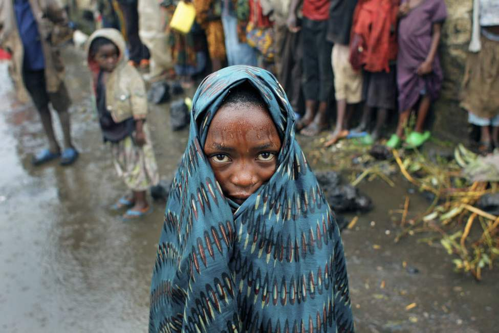 An internally displaced Congolese child waits with others in the rain for aid to be distributed in Kibati, north of Goma, eastern Congo. Drenching rain punctuated by bursts of thunder and forked lightning add to the misery of some of the 280,000 refugees from Congo's eastern rebellion, whose plight is highlighted by a visit from the U.N. humanitarian chief Baroness Valerie Amos. (AP Photo/Jerome Delay)