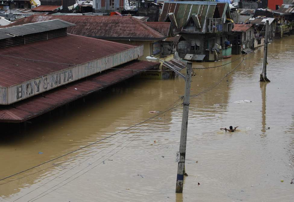 A man swims along a flooded area in Marikina City, east of Manila, Philippines. Widespread flooding that killed at least 23 people, battered a million others and paralyzed the Philippine capital briefly eased Wednesday, allowing rescuers on rubber boats to reach a large number of distressed residents still marooned in submerged villages. (AP Photo/Aaron Favila)