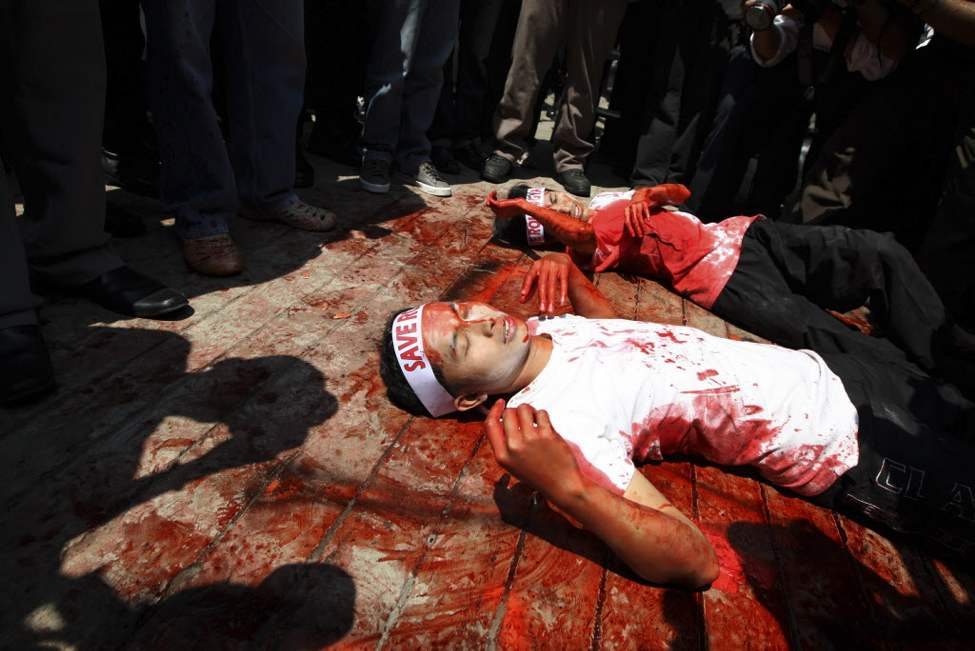 Covered in mock blood, Muslim protesters perform a die-in during a rally outside the embassy of Myanmar in Jakarta, Indonesia. Dozens of people staged the rally calling for an end to the violence against ethnic Rohingya Muslims in Rakhine State of Myanmar. (AP Photo/Dita Alangkara)