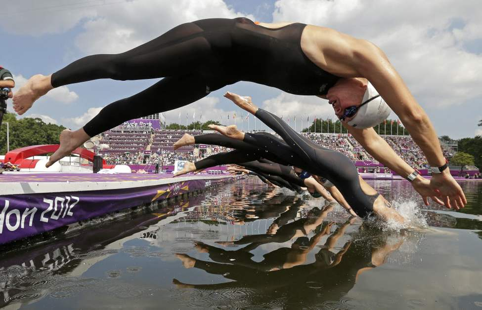 Germany's Angela Maurer, front, and other athletes dive into the Serpentine at Hyde Park as they compete in the women's marathon swimming competition at the 2012 Summer Olympics. (AP Photo/Charlie Riedel)