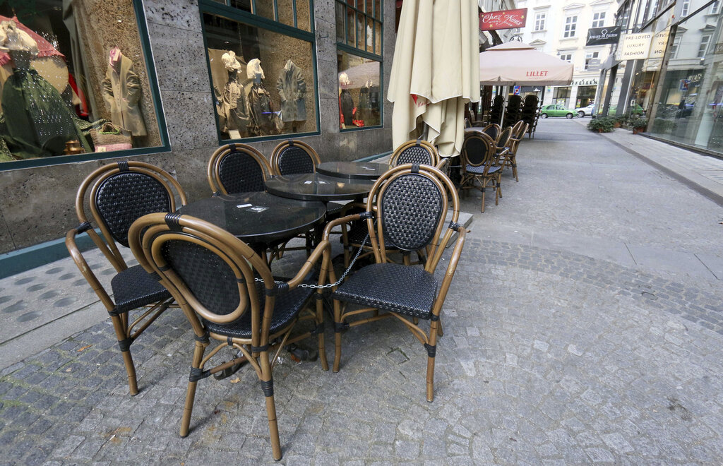 Locked chairs and tables outside a coffee house in Vienna, Austria, last November. Austria's economy took the second-worst hit in the European Union last fall, thanks in large part to reduced tourism during lockdowns. (AP Photo/Ronald Zak)